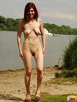 A sexy redhead gets nude at the beach and shows off her perfect shaved pussy.
